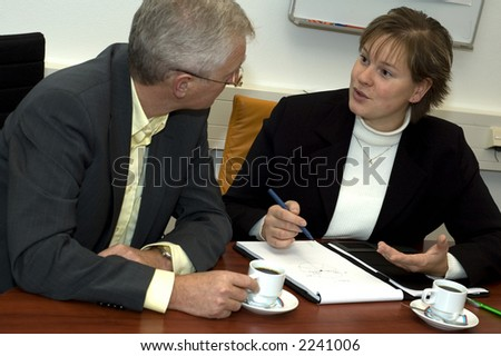 Two business people discussing. Focus is on the woman.