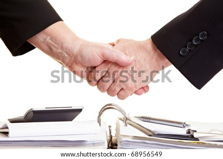 Two business people doing handshake over a bunch of files