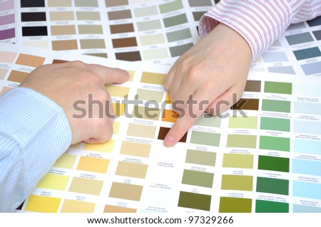 Two business people hands pointing to color samples