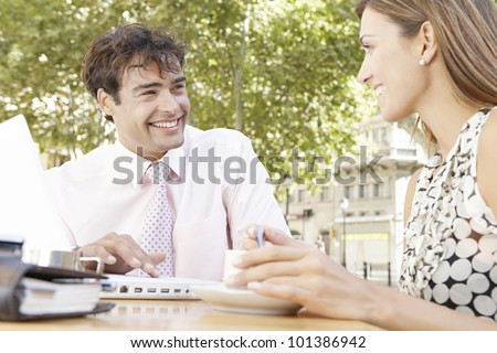 Two business people having a meeting in an outdoors cafeteria in the city, smiling.