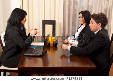 Two business people having an interview with a manager woman in a workplace