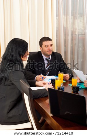 Two business people having discussion with others at meeting