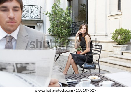 Two business people in a classic building's terrace reading the newspaper and talking on the cell phone.
