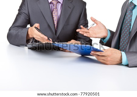 Two business people in elegant suits sitting at desk working in team together and discussing the problem holding clipboard, folder with papers, document, business plan. Isolated over white background.