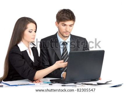 Two business people in elegant suits sitting at desk working in team together, discussing the problem, point finger working on laptop, clipboard with papers, document, Isolated over white background