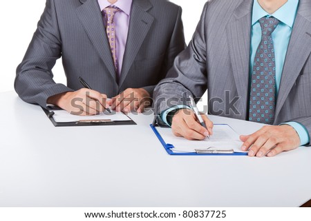 Two business people in elegant suits sitting at desk working in team together, working with documents sign up contract, on clipboard, folder with papers, business plan. Isolated over white background.