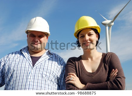 two business people in front of a wind park - stock photo