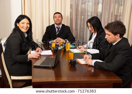 Two business people laughing and other two business people being serious and writing at business meeting