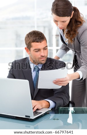 Two business people looking at a paper while working on the laptop in the office