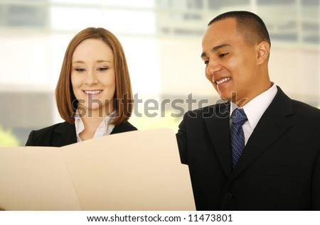 two business people looking at folder as if they are discussing or checking report