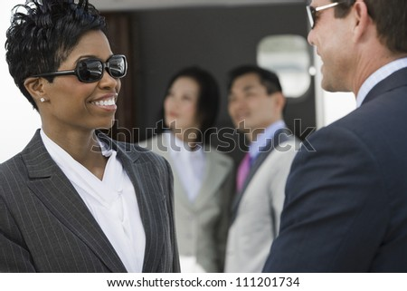 Two business people looking each other with colleagues in the background