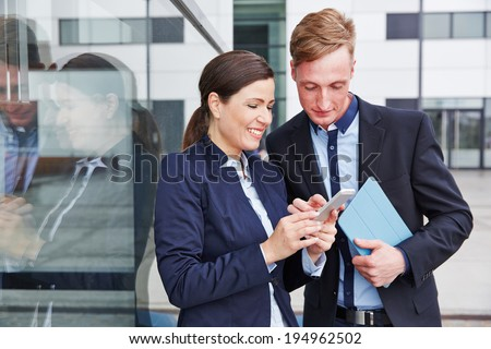 Two business people looking together at smartphone in the city