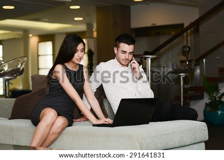 two business people man and woman working on a computer while waiting in airport lounge