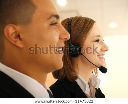 two business people, one of them wearing headset as customer service in light office environment looking to the side as if they are on meeting