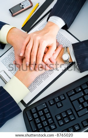 Two business people's hands on the contract with a pen, a cell, a ruler, a pencil and a keyboard at the backgrounds