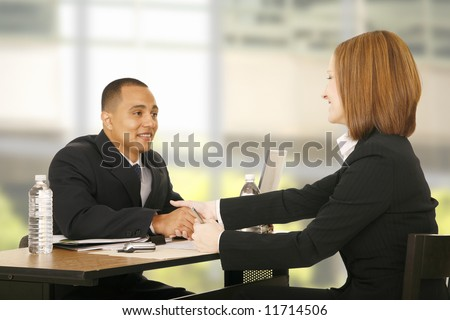 two business people shaking hand over table. focus on the woman. concept for business deal, team work, selling or agreement