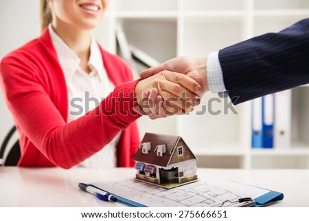 Two business people shaking hands as successful agreement in real estate agency office. Concept of housing purchase and insurance.