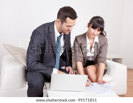 Two business people sitting in the couch discussing - stock photo