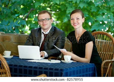 Two business people sitting with notebook
