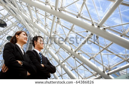 two business people stand in modern office