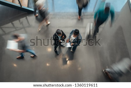 Two business people standing in the lobby of an office looking at a tablet while people are walking past in a blur