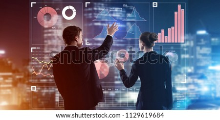 Two business people standing with back and working together with virtual screen #1129619684