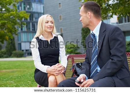 Two business people talking outside on a park bench