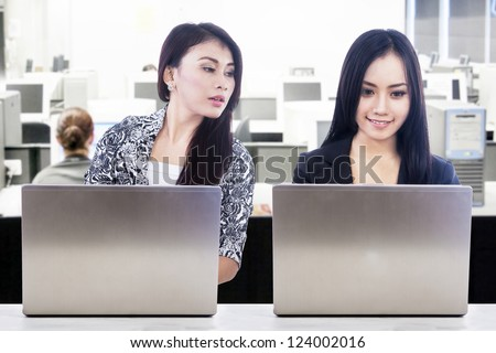 Two business people typing on laptop computer