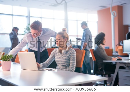 two business people using laptop  preparing for next meeting and discussing ideas with colleagues in the background #700955686