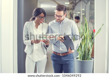 Two business people working together with documents while having informal meeting in office hallway. #1046049292