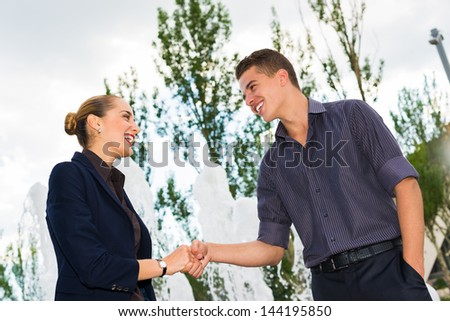 Two business people, young businessman and businesswoman shaking hands on a light background.