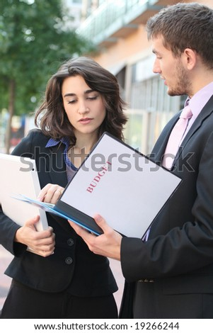 Two business people, young professionals, outdoors, at work - looking at budget. Suitable for a variety of political, economic themes