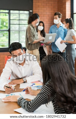 Two business person brainstorm in meeting room with group of interracial business worker team working in background. They wear face mask in new normal office  prevent coronavirus COVID-19 spreading