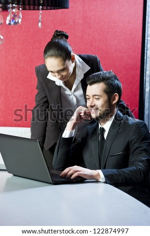 Two business persons posing in office with lap top.