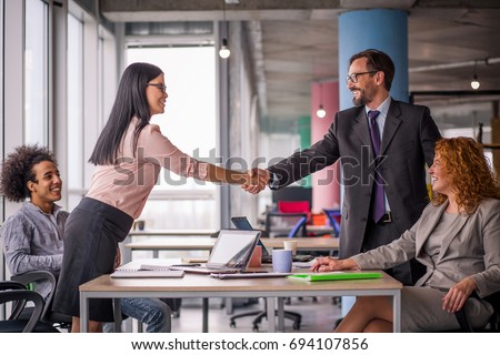 Two business teams successfully negotiating, shaking hands. At meeting table business groups shaking hands on completed deal. Man and woman handshake. #694107856