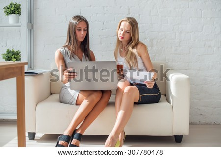 Two business woman friendly discussion during break in office using notebook and drinking coffee