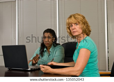 Two business woman in a conference room working on a laptop