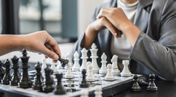 Two business women competitors playing chess board game, business competition concept, business plan to be the number one company, competitor analysis and problem solving. For always good results.