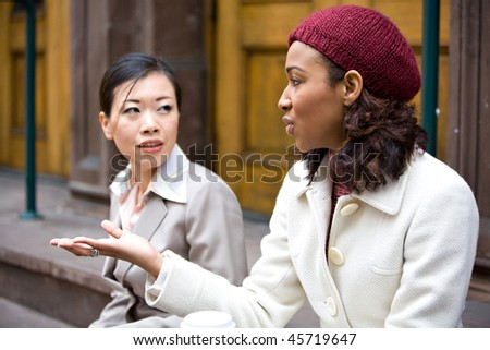 Two business women having a casual chat or discussion in the city perhaps on their lunch break. Shallow depth of field.