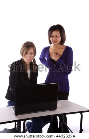 Two business women looking at something on the computer with sad expressions on their faces.