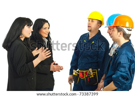 Two business women managers talking with team of constructor workers men isolated on white background
