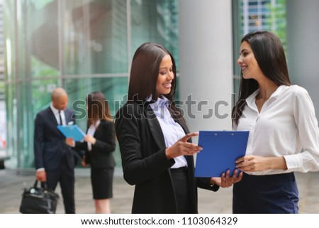 Two business women of different ethnicities talk about finance looking at the patterns of economic markets and banks, and in the background a group of multi-ethnic business people.  #1103064329