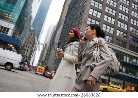 Two business women walking in the big city. One woman is on her cell phone.  Slightly shallow depth of field. - stock photo