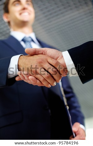 Two businessman happily shaking hands indicating successful negotiations