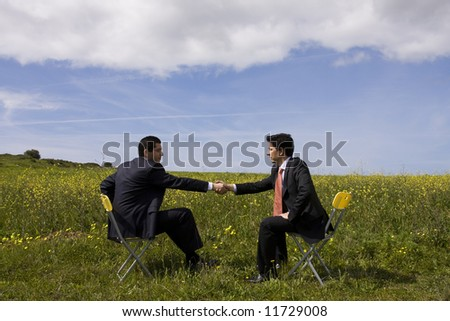 two businessman making a deal with a handshake at the field