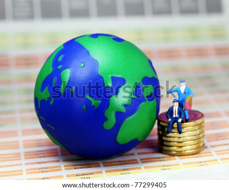 Two businessman one sat and one stood on a pile of golden coins next to a globe of the world, with Europe prominent.