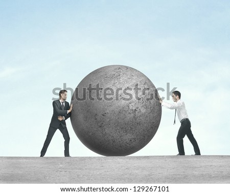 two businessman pushing concrete ball