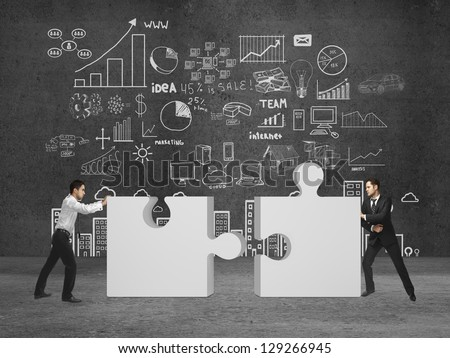 two businessman puts puzzle on concrete room - stock photo