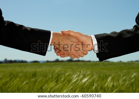 Two businessman shake hands with a land and property field background with plenty of copy space. - stock photo
