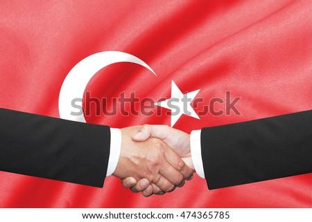 two businessman shakehand over turkey flag